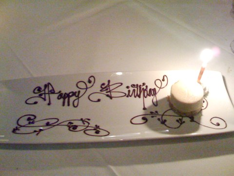 a tiny disc of custard on a large dish upon which 'happy birthday' is written with chocolate