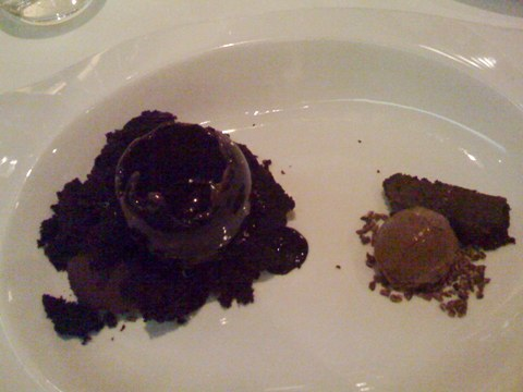 a partially melted hollow chocolate sphere with a dollop of fudge within, surrounded by rich chocolate cake on the left; on the right, a dollop of black olive ice cream surrounded by minced cacao nibs, and a small, thin brownie slice