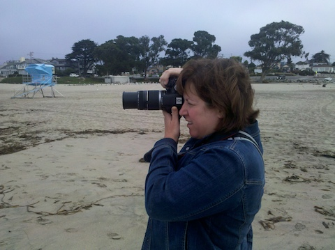 kim on the beach, taking pictures in portrait mode with her DSLR + zoom lens